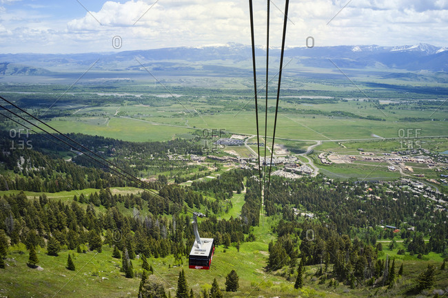 United States, Wyoming, Teton Village - June 2, 2016: Aerial tram with Jackson Hole Valley and Teton Village below