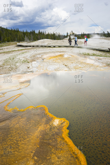United States, Wyoming, Yellowstone National Park - June 5, 2016: Three people walking in upper geyser basin, Yellowstone National Park