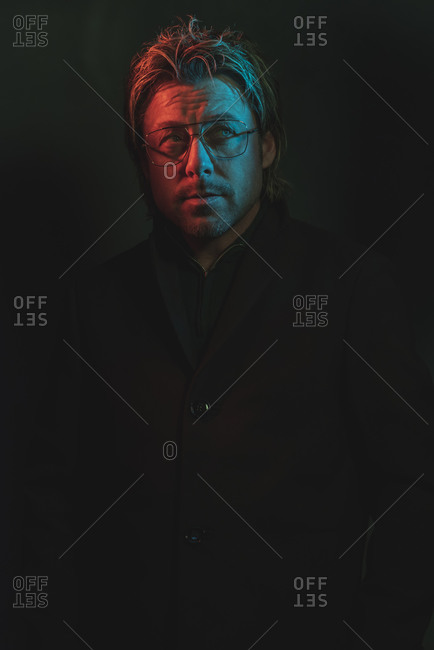 Man wearing glasses with red and blue lights illuminated on his face looking away