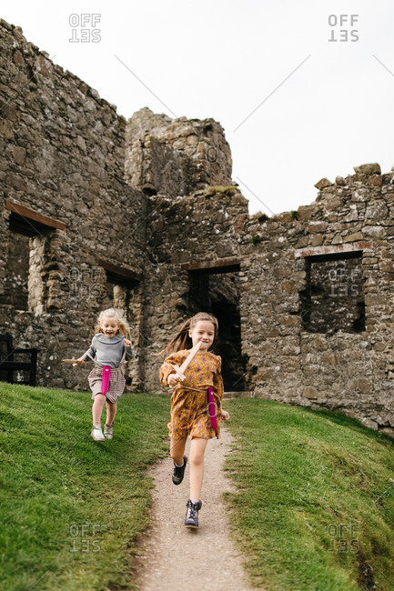 Two girls running with toy swords by the remains of the Dunluce Castle in Northern Ireland