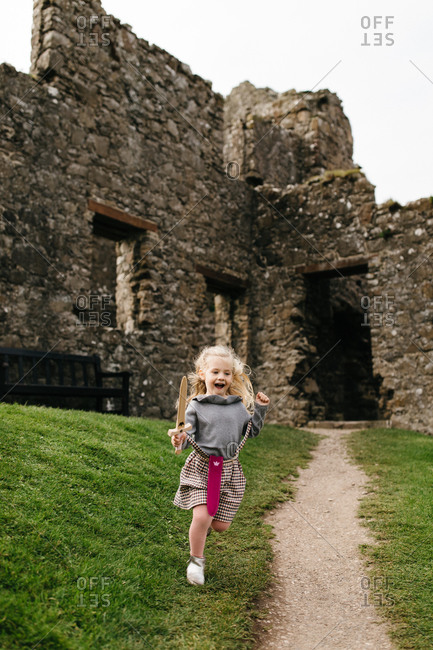 Little blonde girl running with toy sword by the remains of the Dunluce Castle in Northern Ireland