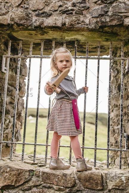 Little blonde girl standing with toy sword by bars at the remains of the Dunluce Castle in Northern Ireland