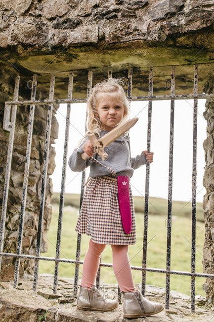 Little girl grimacing while playing with toy sword at the remains of the Dunluce Castle in Northern Ireland