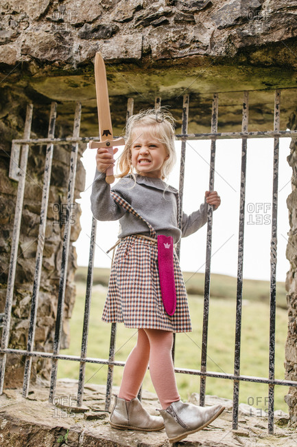 Girl grimacing while playing with toy sword at the remains of the Dunluce Castle in Northern Ireland