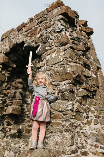 Little blonde girl holding a toy sword at the remains of the Dunluce Castle in Northern Ireland