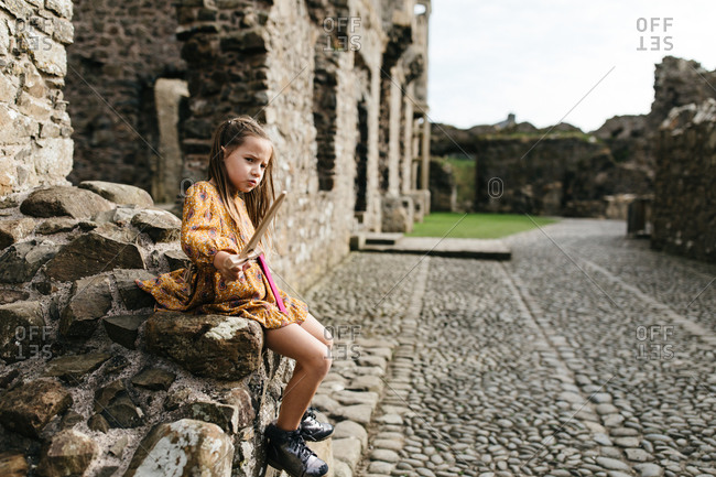 Young girl holding a toy sword at the remains of the Dunluce Castle in Northern Ireland