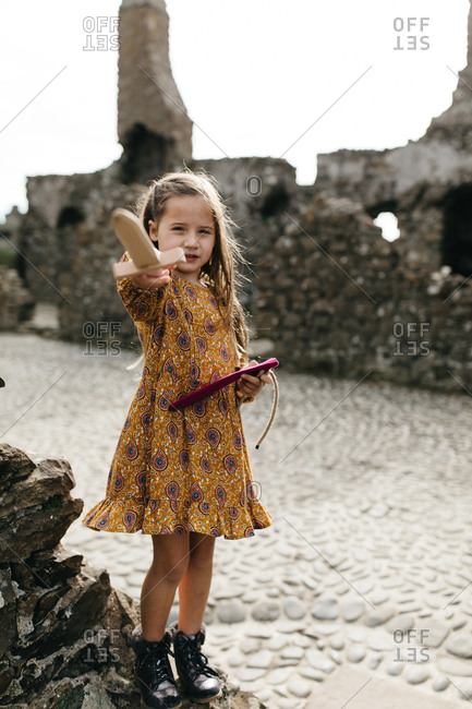 Young girl holding a wooden sword at the remains of the Dunluce Castle in Northern Ireland