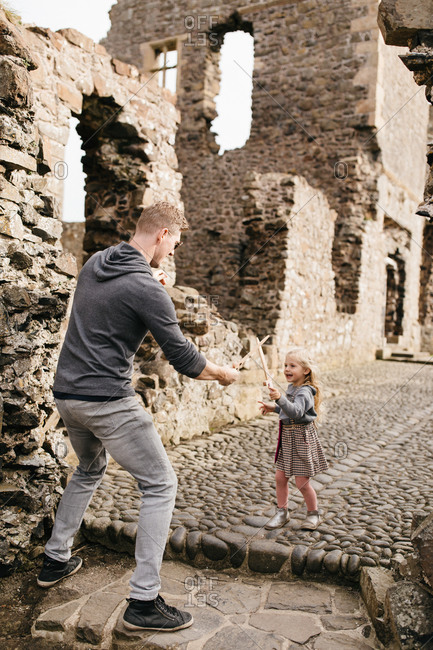 Father and daughter playing with toy swords at the remains of the Dunluce Castle in Northern Ireland