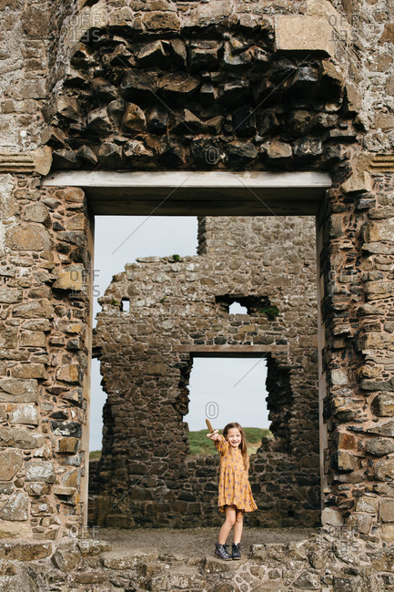 Young girl holding up a wooden sword at the remains of the Dunluce Castle in Northern Ireland