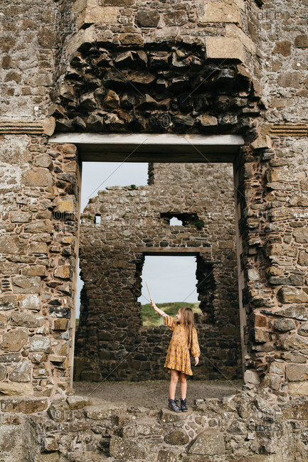 Little girl holding up a wooden sword at the remains of the Dunluce Castle in Ireland