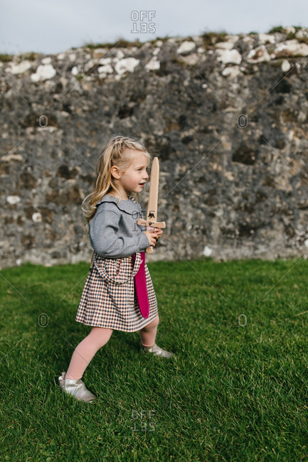 Blonde girl holding a toy sword at the remains of the Dunluce Castle in Northern Ireland