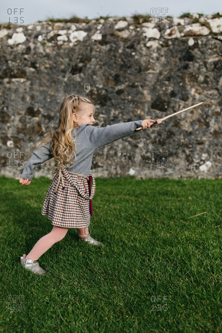 Blonde girl pointing a toy sword at the remains of the Dunluce Castle in Northern Ireland