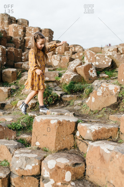 Young girl climbing on stones at Giant's Causeway in Northern Ireland