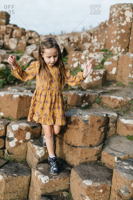 Little girl climbing on stones at Giant's Causeway in Northern Ireland
