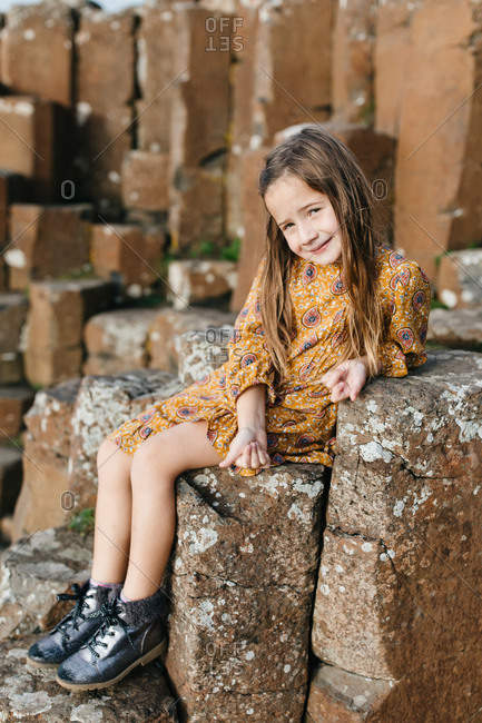 Little girl sitting on stones at the remains of the Dunluce Castle in Northern Ireland