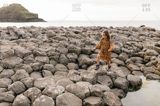 Young girl climbing on stones on the coast of Giant's Causeway in Northern Ireland