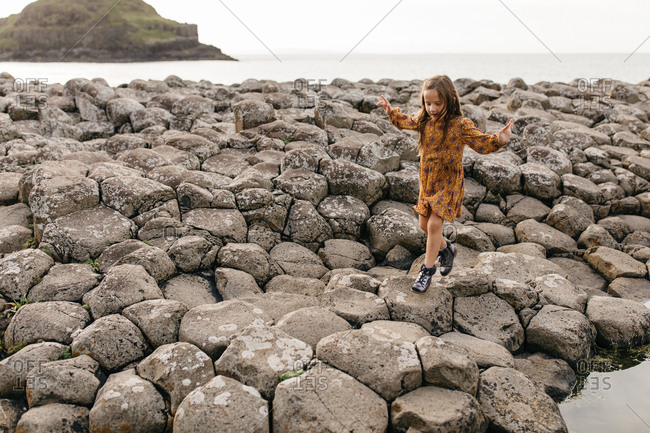 Little girl climbing on stones on the coast of Giant's Causeway in Northern Ireland