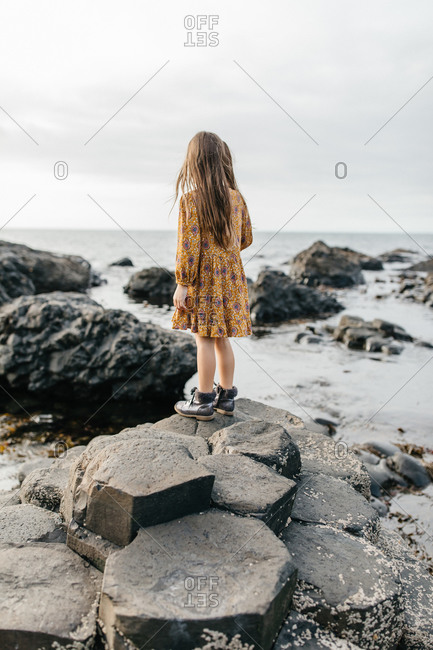Young girl looking out at the ocean from stones on the coast of Giant's Causeway in Northern Ireland