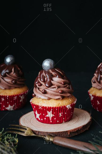 Delicious vegan cupcakes with chocolate cream on black background