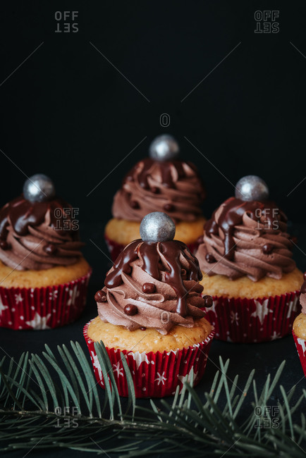 Vegan cupcakes with chocolate cream topped with silver balls on black background