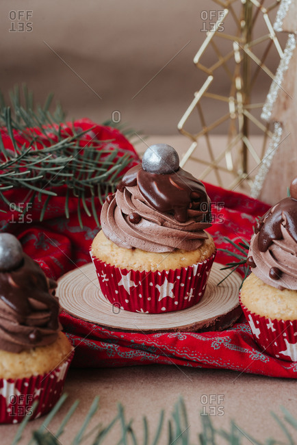 Vegan cupcakes with chocolate cream with Christmas decorations in the background