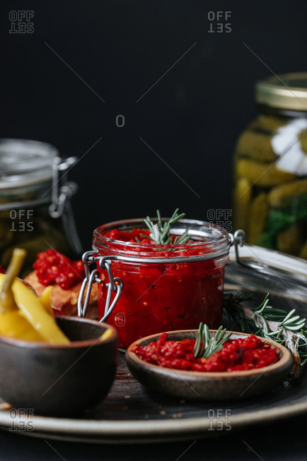 Traditional Serbian paprika dip Ajvar in a jar on a plate on black background
