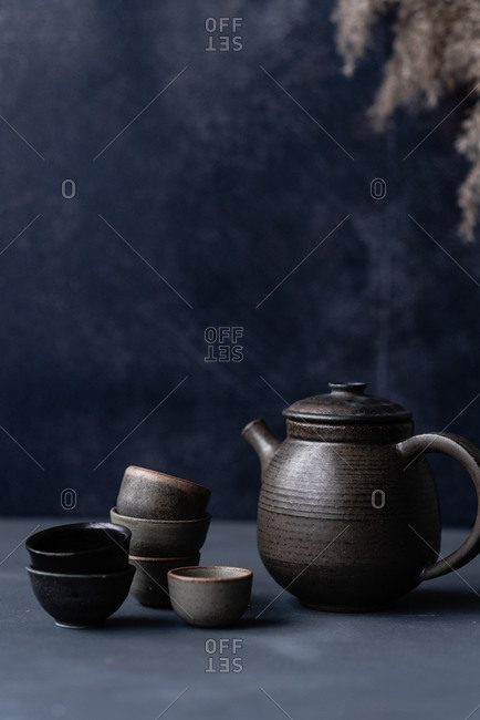 Black handmade ceramic dishes and teapot on dark background