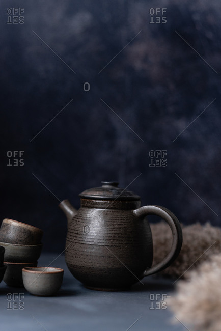 Black handmade ceramic teapot and cups on dark background