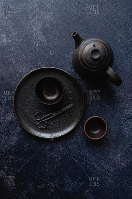 Overhead view of black handmade ceramic dishes on dark background
