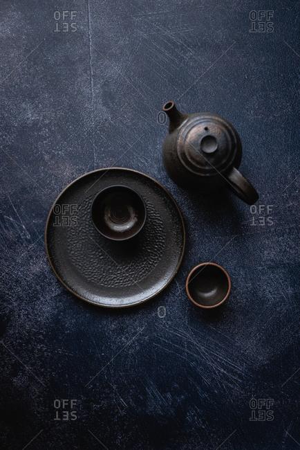 Top view of black handmade ceramic dishes on dark background
