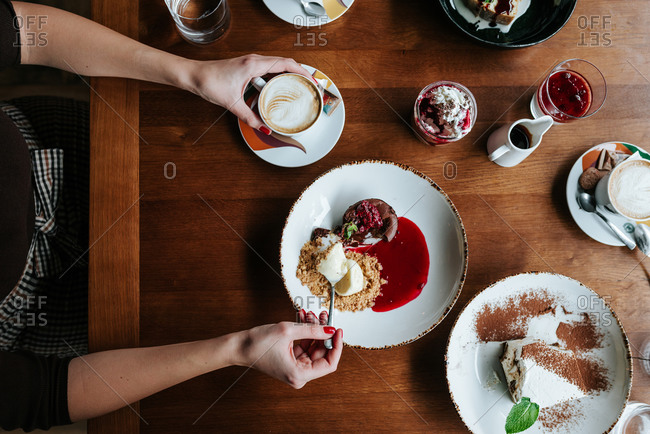 Woman having coffee and eating deserts in restaurant
