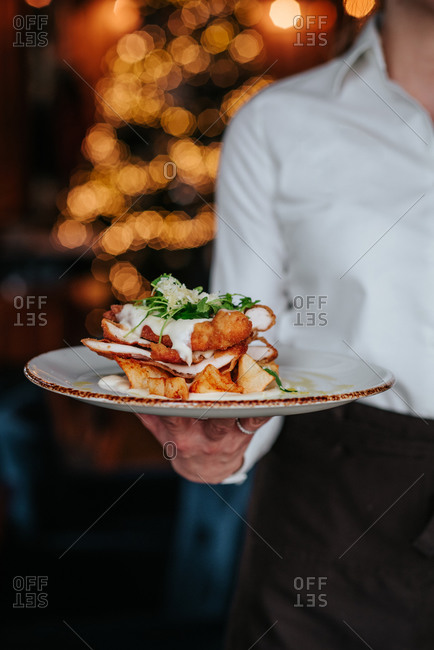 Waiter holding a dish with chicken
