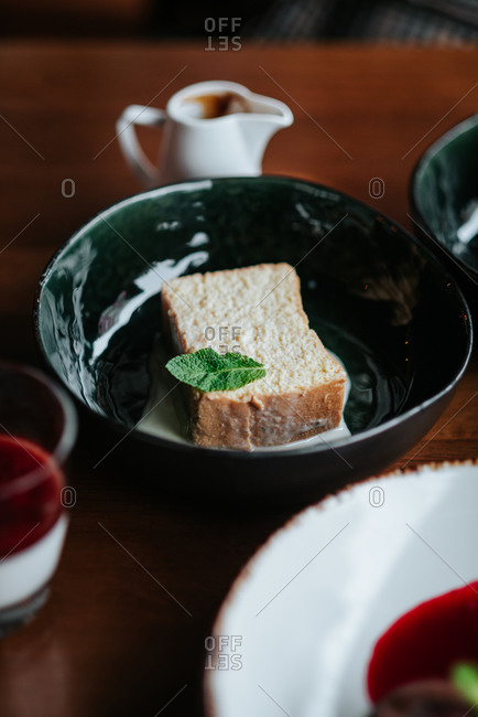 Tres leches cake with a mint leaf on a table