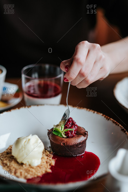 Close up of person taking a bite of cake in a restaurant