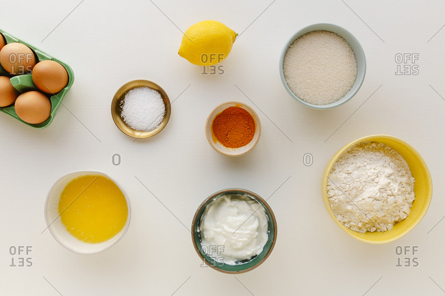 Ingredients for baking a cake prepped in small bowls against a white surface from a top down angle
