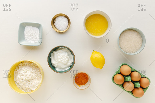 Overhead view of ingredients for baking a cake prepped in small bowls on a white surface