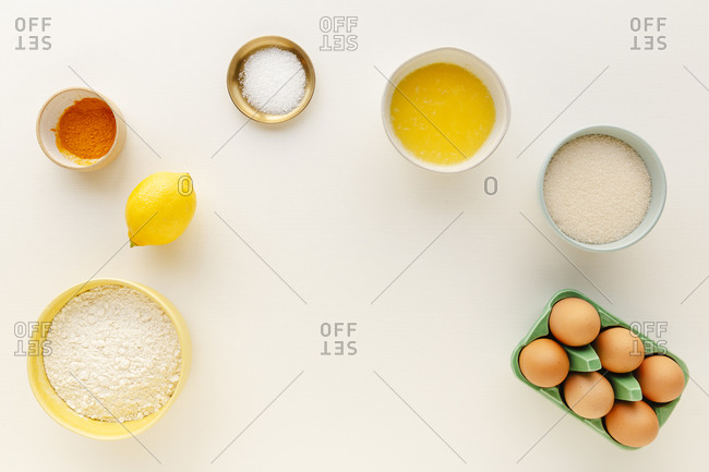 Ingredients for a cake prepped in small bowls in an arc with white copyspace