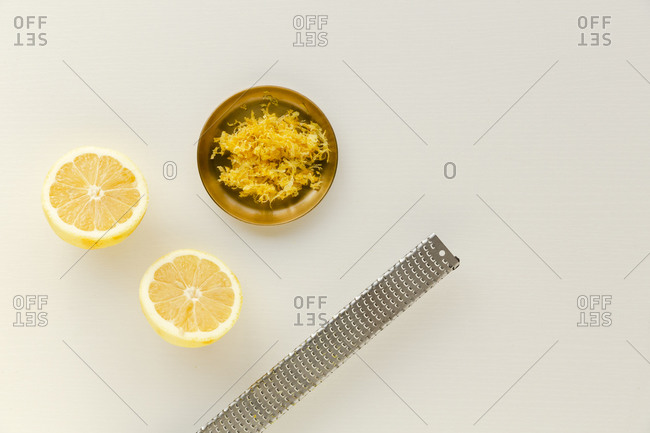 A lemon cut in half next to a small bowl of lemon zest and a microplane