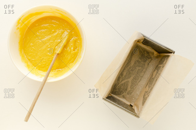 Yellow cake batter in a bowl ready to pour into a loaf pan on a white surface