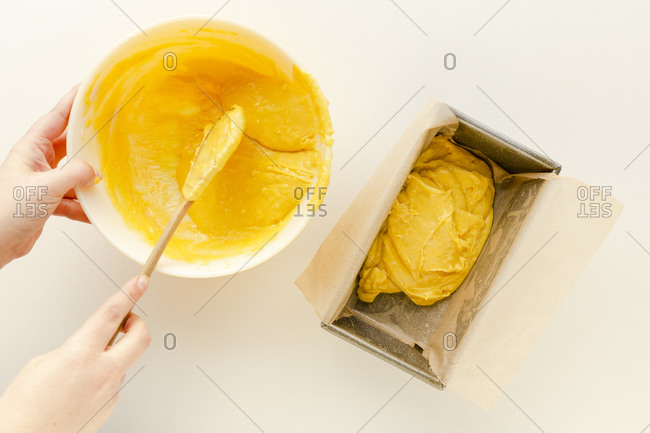 Woman putting yellow cake batter into a loaf pan on a white surface