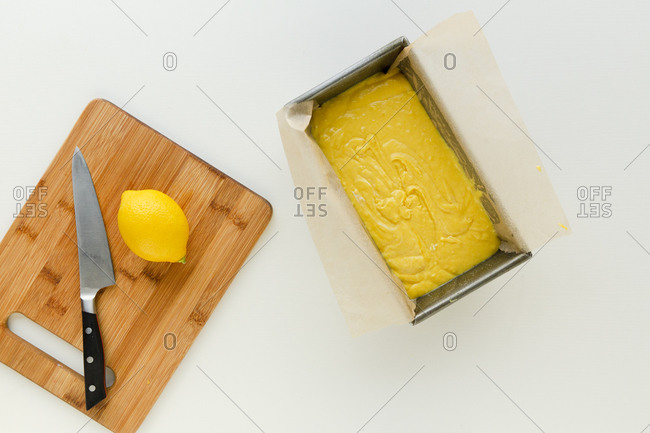 Yellow cake batter in a loaf pan beside cutting board with lemon and knife