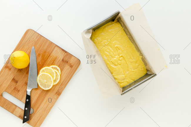 Yellow cake batter in a loaf pan by cutting board with sliced lemon and knife