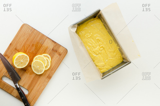 Overhead view of yellow cake batter in a loaf pan by cutting board with sliced lemon