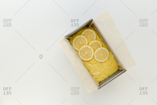 Raw yellow cake batter in a loaf pan against white surface
