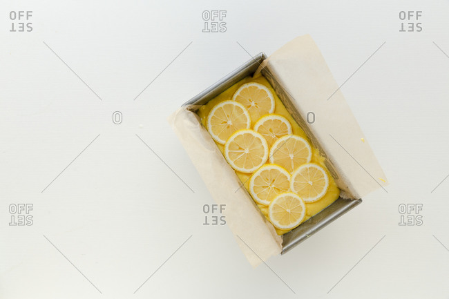 Raw yellow cake mix with lemons in a loaf pan against white surface