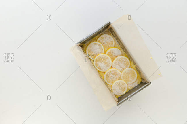Raw cake mix with lemons in a loaf pan against white surface