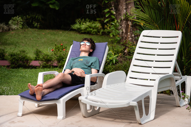 Teen boy relaxing on lounge chair on vacation