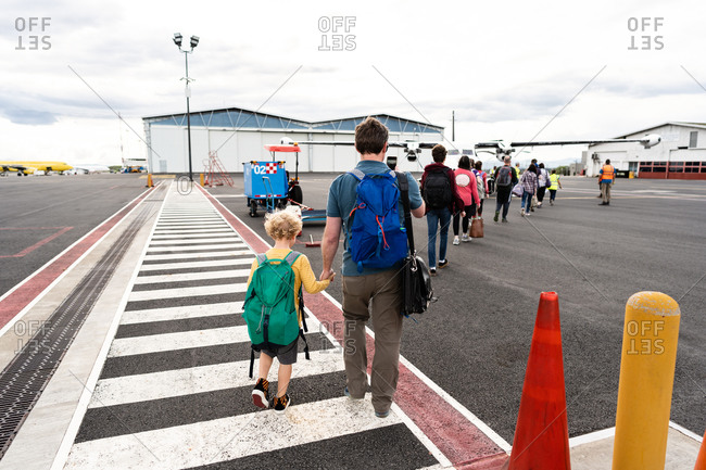 Rear view of family carrying bags outside of airport