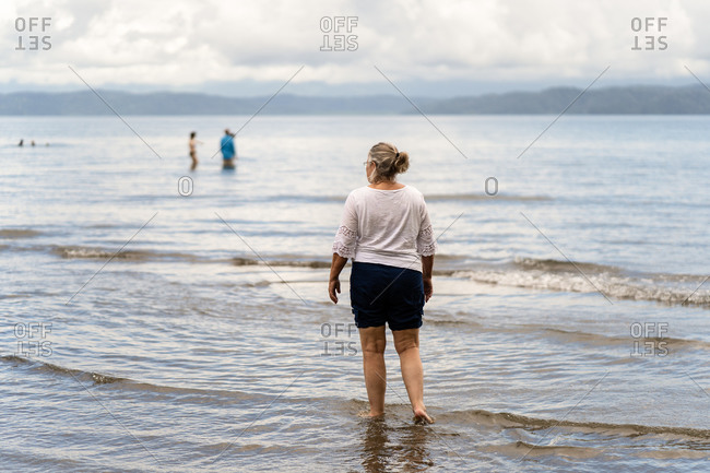 Rear view of senior woman standing in the tide on the coast of Costa Rica