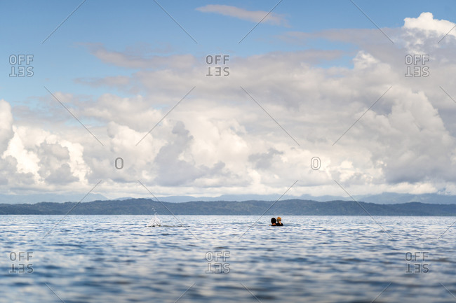 Man holding young boy in the ocean off the coast of Costa Rica